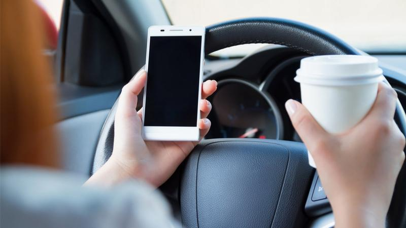 driver with phone and coffee